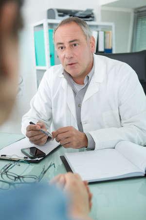 Photo pour maturedoctor is talking to female patient in his office - image libre de droit