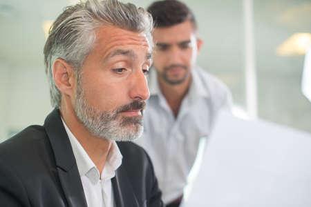 Photo pour nervous man looking how the interviewer is reading his resume - image libre de droit
