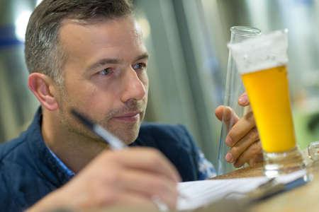 Photo pour Quality control worker inspecting glass of lager - image libre de droit