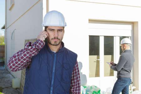 Photo pour supervising a construction using cell phone outdoors - image libre de droit