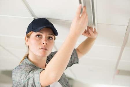 Photo pour woman fixing ceiling fixture - image libre de droit