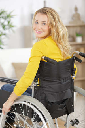 Photo pour smiling young woman in wheelchair looking at camera - image libre de droit