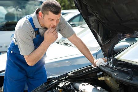 Photo pour mechanic inspecting car engine - image libre de droit