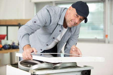 Foto de man fixing something in the kitchen - Imagen libre de derechos