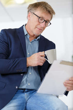 Photo pour smiling businessman holding a clipboard and take away coffee - image libre de droit