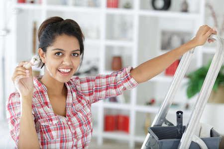 Photo pour happy young woman paints wall at home - image libre de droit