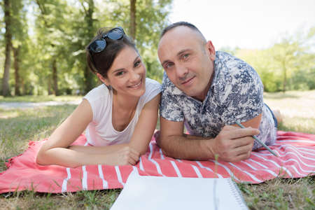 Photo pour mid-adult couple layed on a blanket in the park - image libre de droit