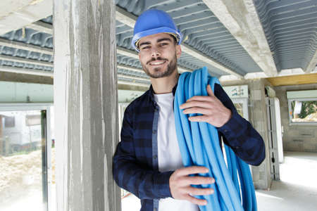 Photo pour young technician holding water pipes indoors - image libre de droit
