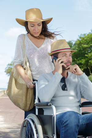Photo pour woman and man in wheelchair using phone at the park - image libre de droit