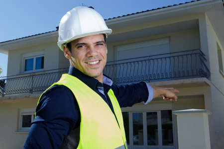 Photo pour suited man wearing hardhat pointing towards residential property - image libre de droit