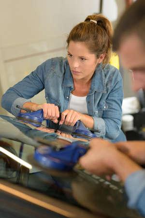 Photo pour garage mechanics fitting new car windshield - image libre de droit