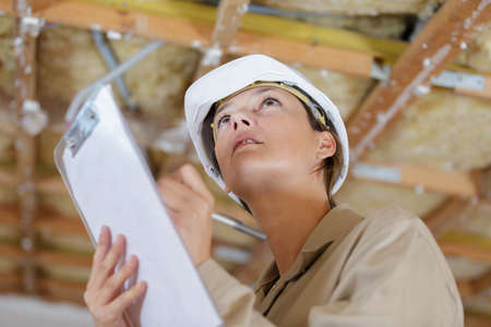 Photo pour female inspector looking at ceiling in property to renovate - image libre de droit