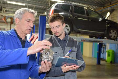 Photo pour intern at automotive garage taking some notes - image libre de droit