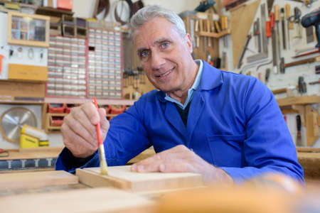 Photo pour portrait of happy senior carpenter varnishing wood in workshop - image libre de droit