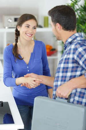 Photo pour man shaking hand with female customer - image libre de droit