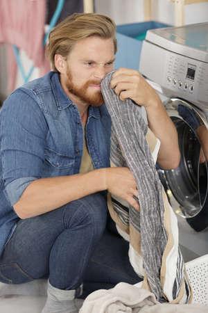 Photo pour a man smelling dirty clothing - image libre de droit