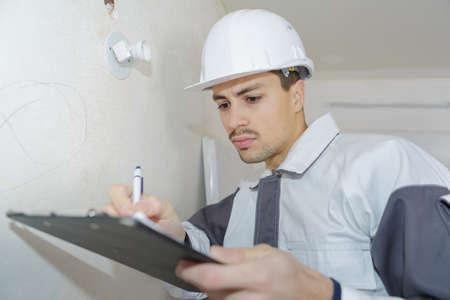 Photo pour male engineer writing on clipboard at construction site - image libre de droit
