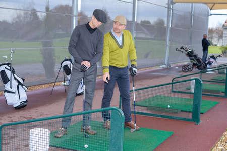 Photo pour two golfers practicing teeing off - image libre de droit