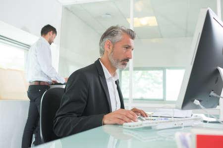 Photo pour cheerful guy sitting in front of desktop computer - image libre de droit