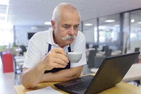 Photo pour senior man holding a cup of coffee - image libre de droit