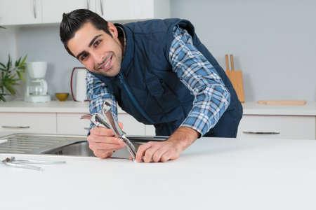 Photo pour Portrait of plumber fitting kitchen tap - image libre de droit