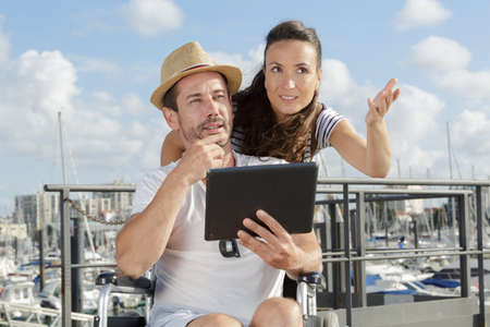 Photo pour young disabled man and his girlfriend with digital tablet - image libre de droit