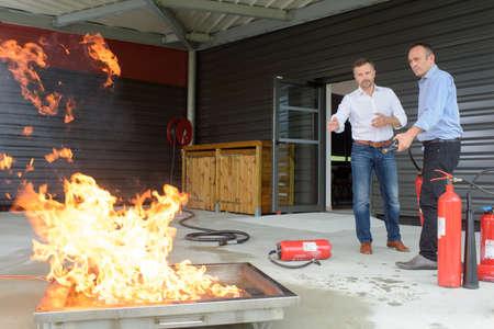 Photo pour 2 workers training in case of fire emergency - image libre de droit