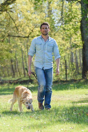 Photo pour man walking his dog at the park - image libre de droit