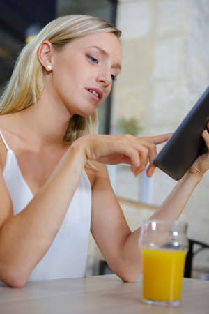 Photo pour woman with juice on table using tablet - image libre de droit