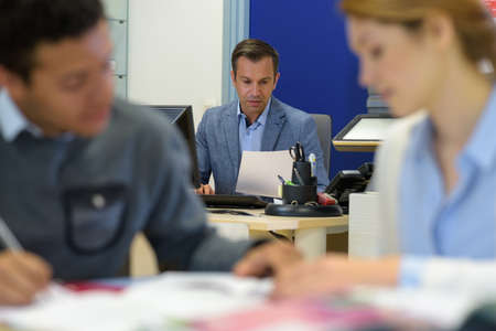 Photo pour people in the office with supervisor on his desk - image libre de droit