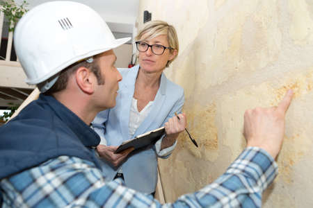 Photo pour contractor inspecting exterior wall of property with suited woman - image libre de droit