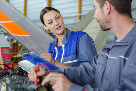 Photo pour aero engineer and apprentice working in hangar - image libre de droit