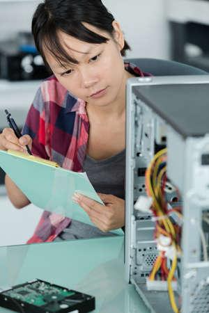 Photo pour computer technician making notes on a clipboard - image libre de droit