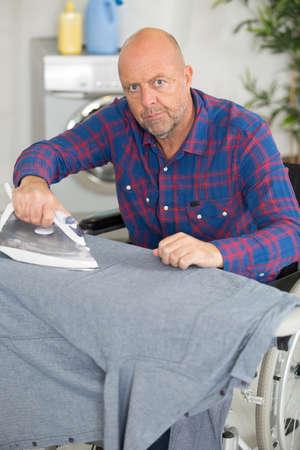 Photo pour disgruntled man in wheelchair using an iron - image libre de droit