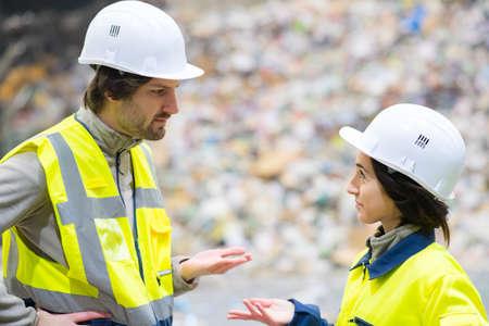 Photo pour workers in conversation in refuse center - image libre de droit