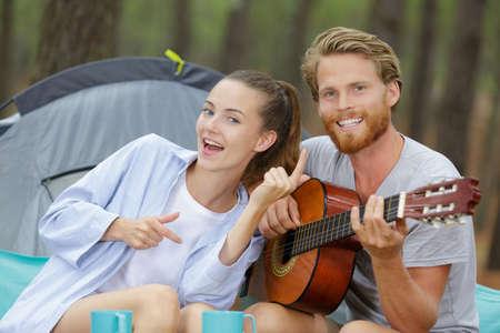 Photo pour young smiling couple next to a camping tent - image libre de droit