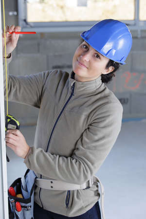 Photo pour beautiful woman builder in helmet with ruler - image libre de droit