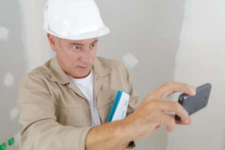 Photo pour senior builder taking photograph with smartphone - image libre de droit