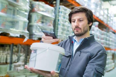 Photo pour storeman scanning product in plastic container with smartphone - image libre de droit