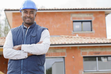 Photo pour proud and confident constructor standing in front of new house - image libre de droit