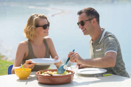 Photo pour happy couple eating salad for dinner at a restaurant terrace - image libre de droit