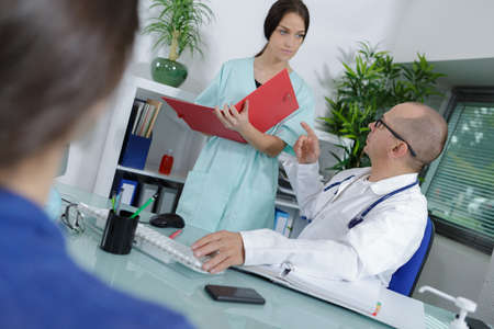 Photo pour doctors and nurse talking in office meeting - image libre de droit