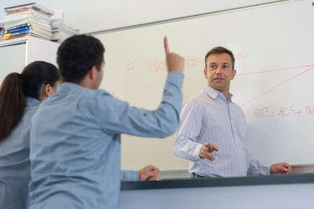 Photo pour Student raising his hand during class - image libre de droit