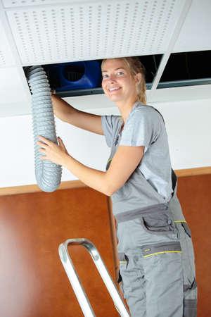 Photo pour woman fitting ventilation hose into roof space - image libre de droit