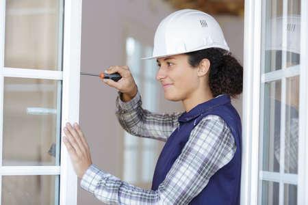 Photo pour young woman unscrews the fixing screws of the window handle - image libre de droit