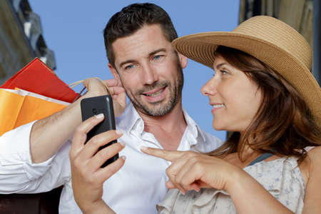 Photo pour couple in city street looking at smartphone screen - image libre de droit