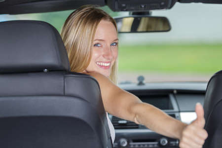 Photo pour beautiful smiling girl with thumbs up in a car - image libre de droit