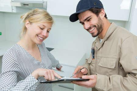 Photo pour woman signing receipt for plumber service - image libre de droit
