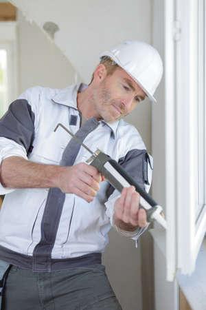 Photo pour construction worker installing window in house - image libre de droit
