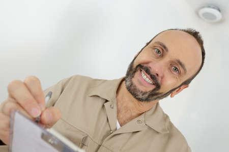 Photo pour mature worker in a beige uniform writing on a clipboard - image libre de droit